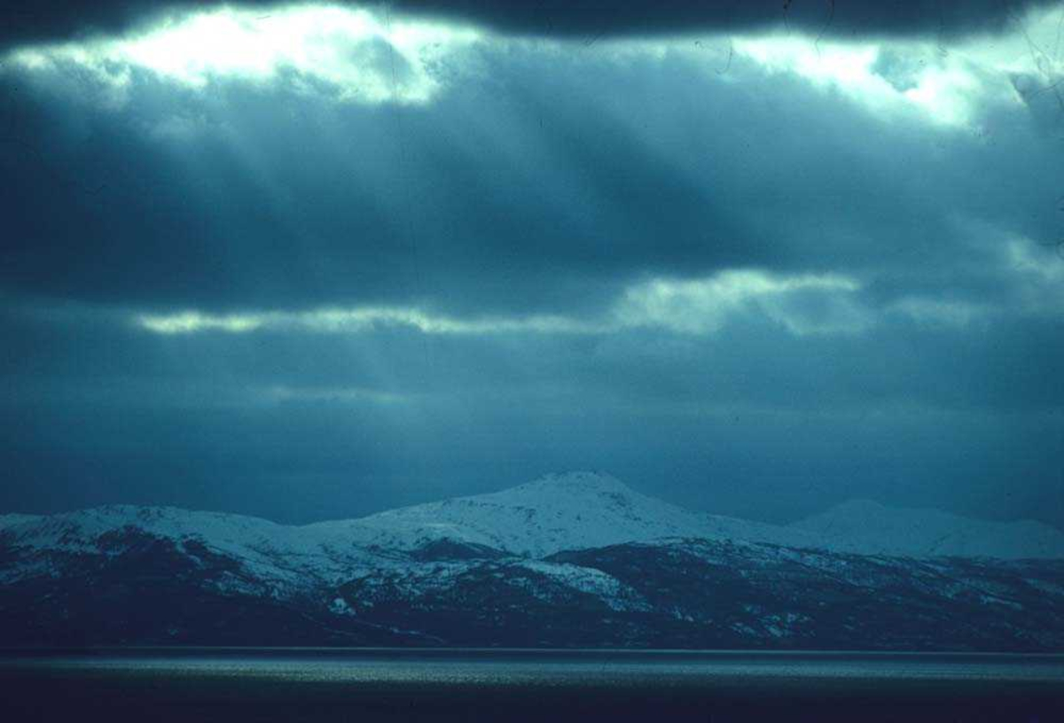 Landskap. Tunge skyer over en fjord og snødekkete fjell, et sted i Troms.