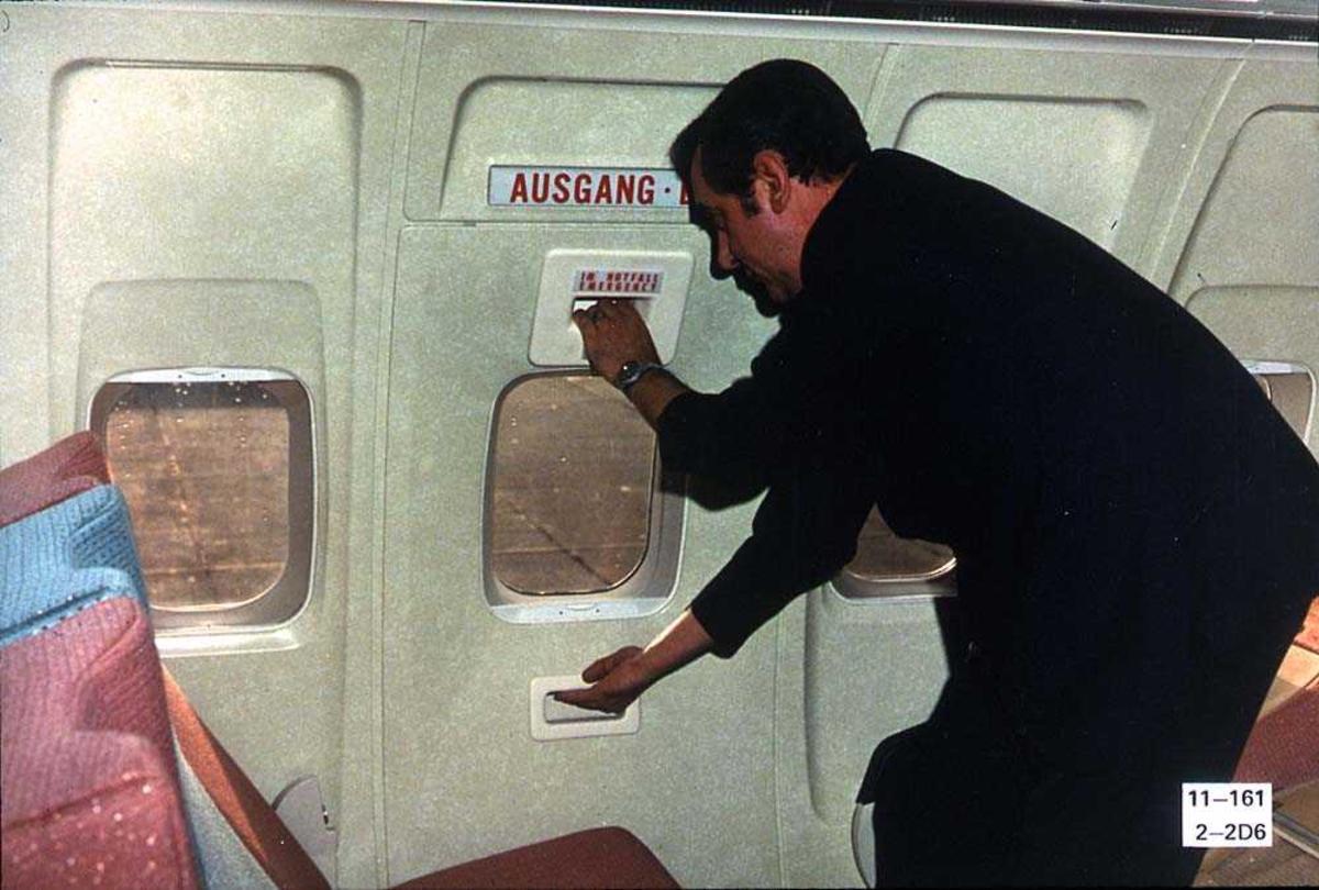 En person inne i kabinen på ett fly, Boeing 737-200, som åpner en nødutgangsdør.