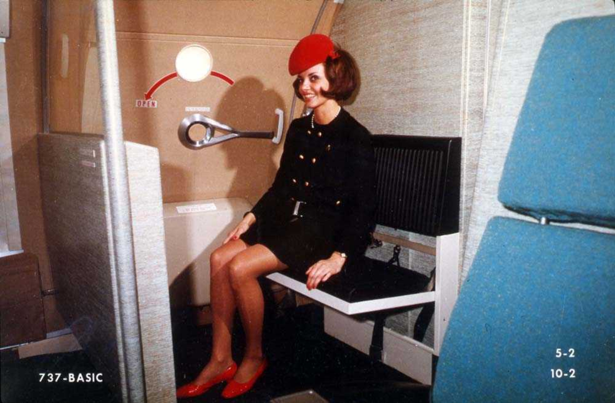 En person som sitter på et klappsete ombord i et fly, Boeing 737, ved en utgang.