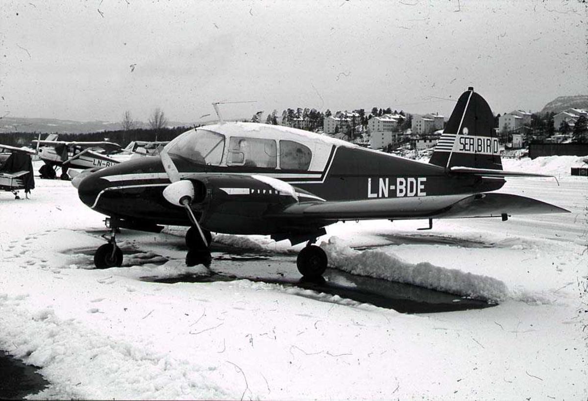 Lufthavn. Ett fly på bakken, Piper PA-23-160D Apache LN-BDE. Flere fly og bygninger i bakgrunnen. Snø på bakken.
