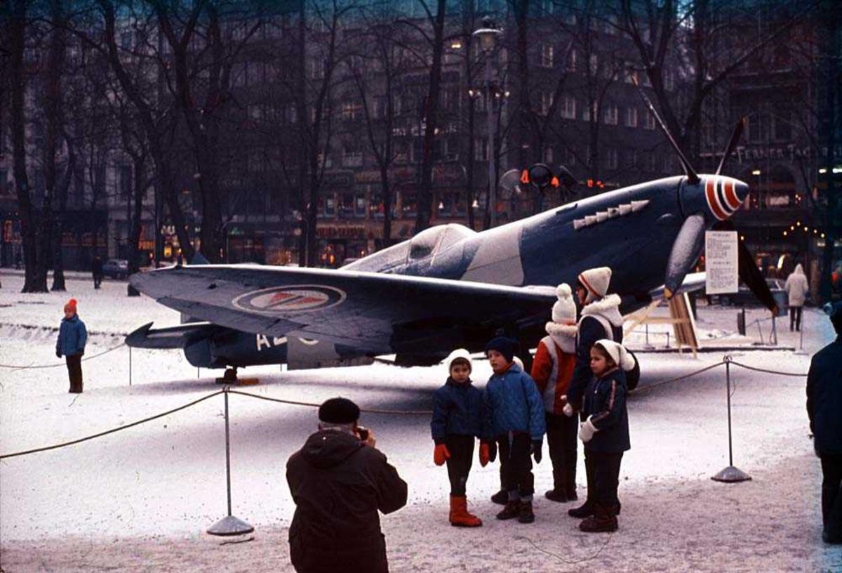 Ett fly som står utstillt i en park, Spitfire Mk P. R. XI AZ-B. Flere personer rundt flyet, bygninger i bakgrunnen. Snø på bakken.