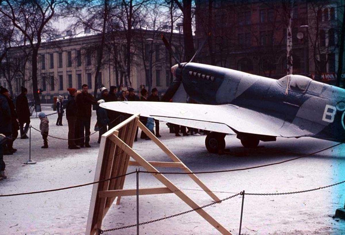 Ett fly som står utstillt i en park, Spirtfire Mk P. R. XI AZ-B. Flere personer og bygninger i bakgrunnen. Snø på bakken.
