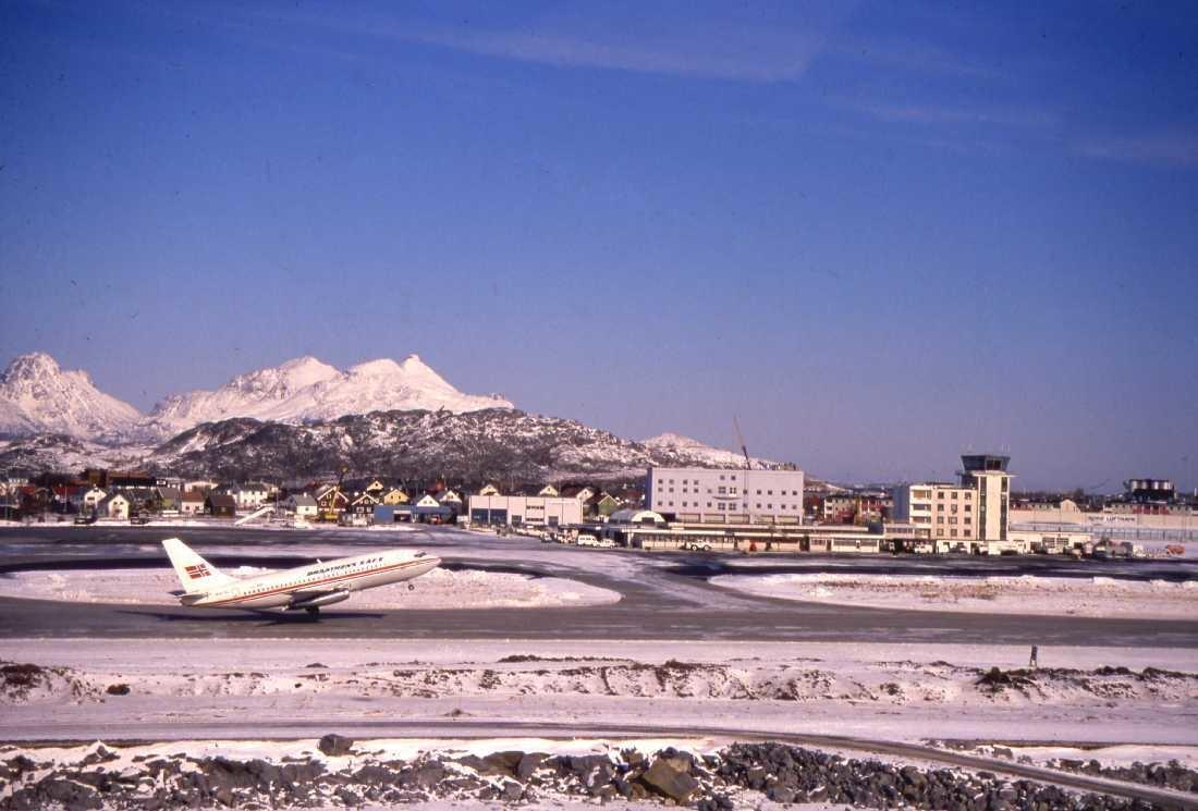 Lufthavn - flyplass. Bodø. Et Braathen fly under take off runway 08. Den nye flytårn bygningen under oppføring til venstre for det gamle flytårnet. I bakgrunn et vinterkledd Landegode.