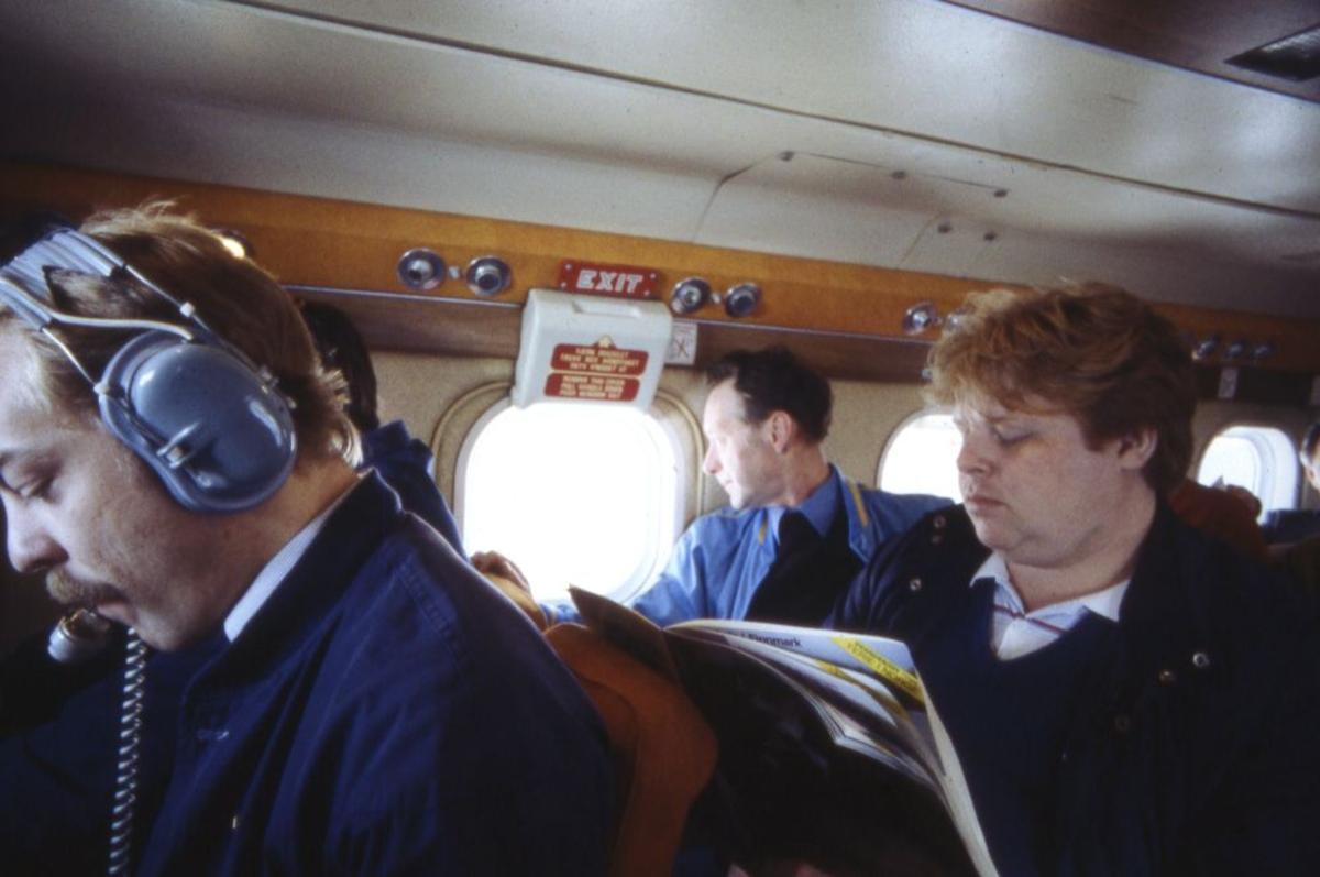 Luftfoto. Et fly, DHC-6-300 Twin Otter fra Widerøe. Motiv fra kabin med passasjerer. På første stolrad med headset flyger under opplæring (supernummerary).