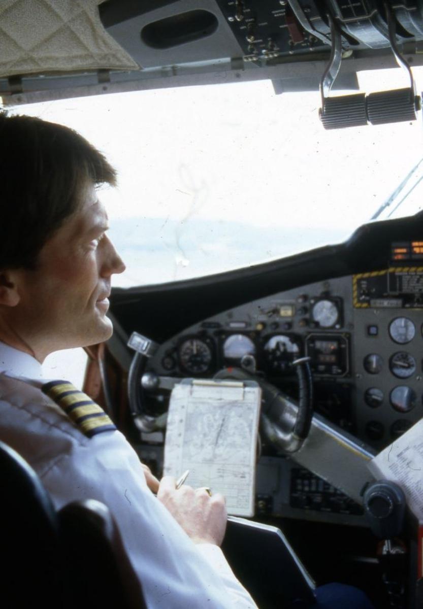 Luftfoto. I cockpit på et fly, DHC-6-300 Twin Otter fra Widerøe, sitter en flyger (pilot).