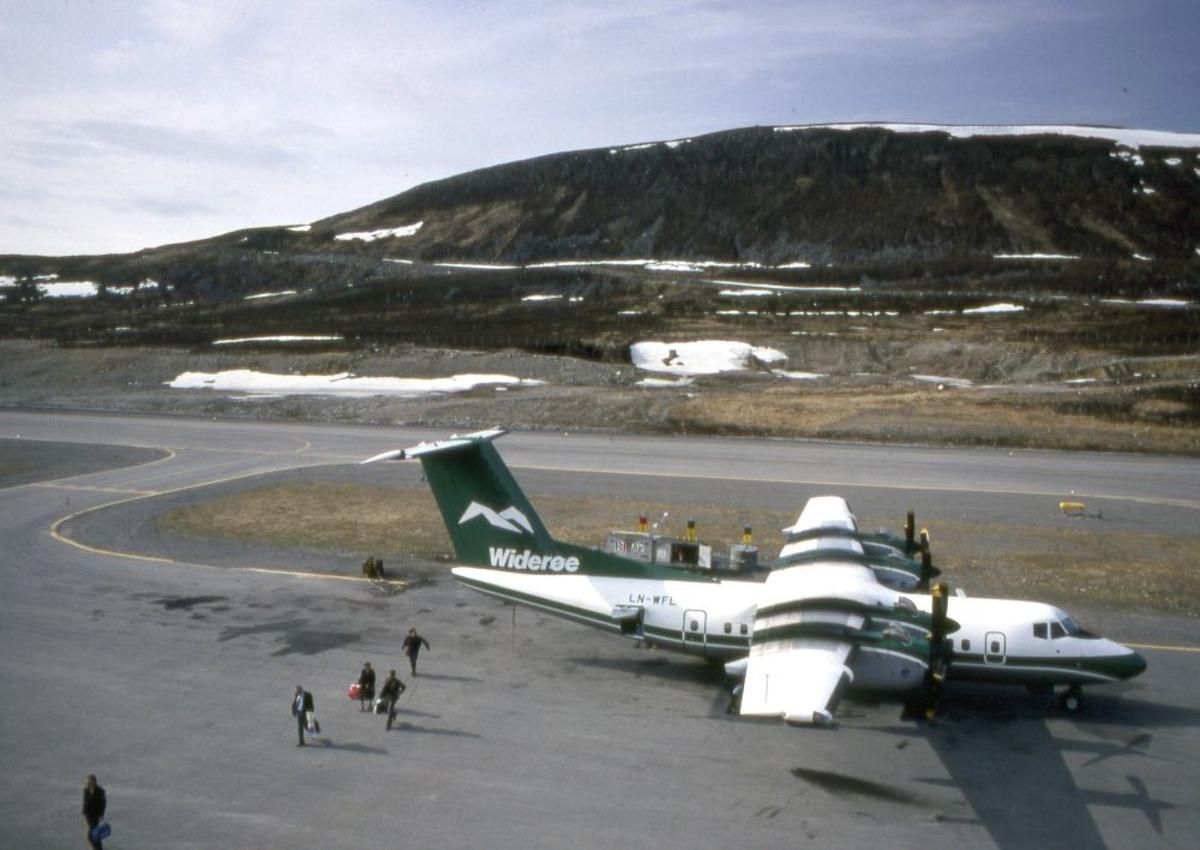 Lufthavn (flyplass). Et fly, LN-WFL, DHC-7-102 Dash 7 fra Widerøe parkert. Flere passasjerer går fra flyet.