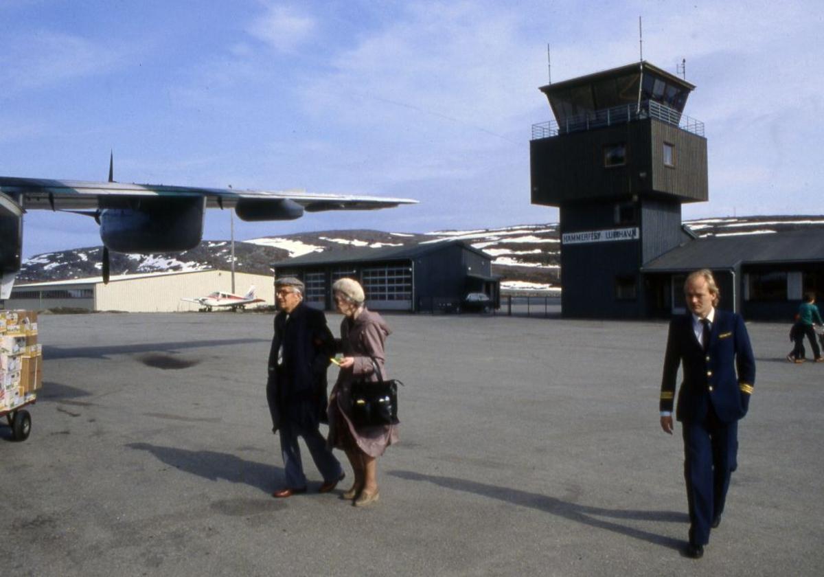 Lufthavn (flyplass). Høyre vinge til et fly, LN-WFL, DHC-7-102 Dash 7 fra Widerøe. To passasjerer og en flyger (pilot) går til flyet.