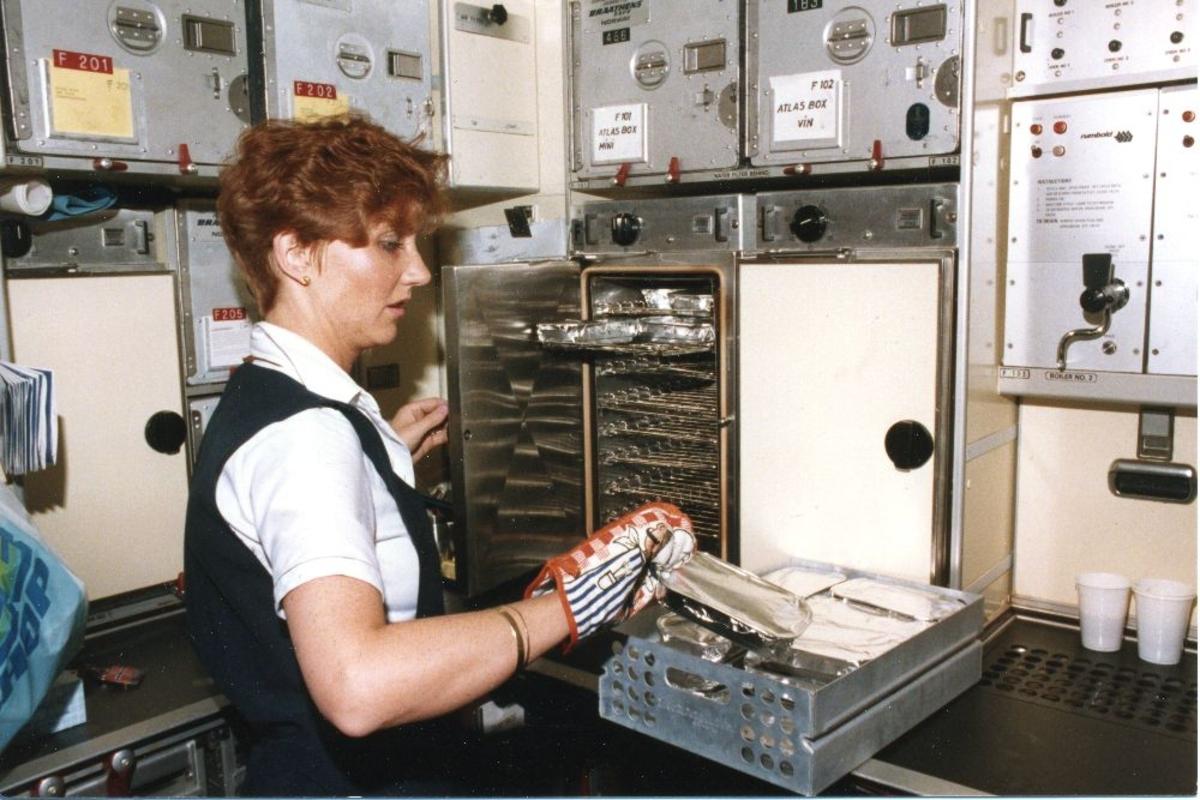 Lufthavn/Flyplass. En kabinansatt klargjør mat i pantry til et fly, Boeing 767 fra Braathens SAFE.