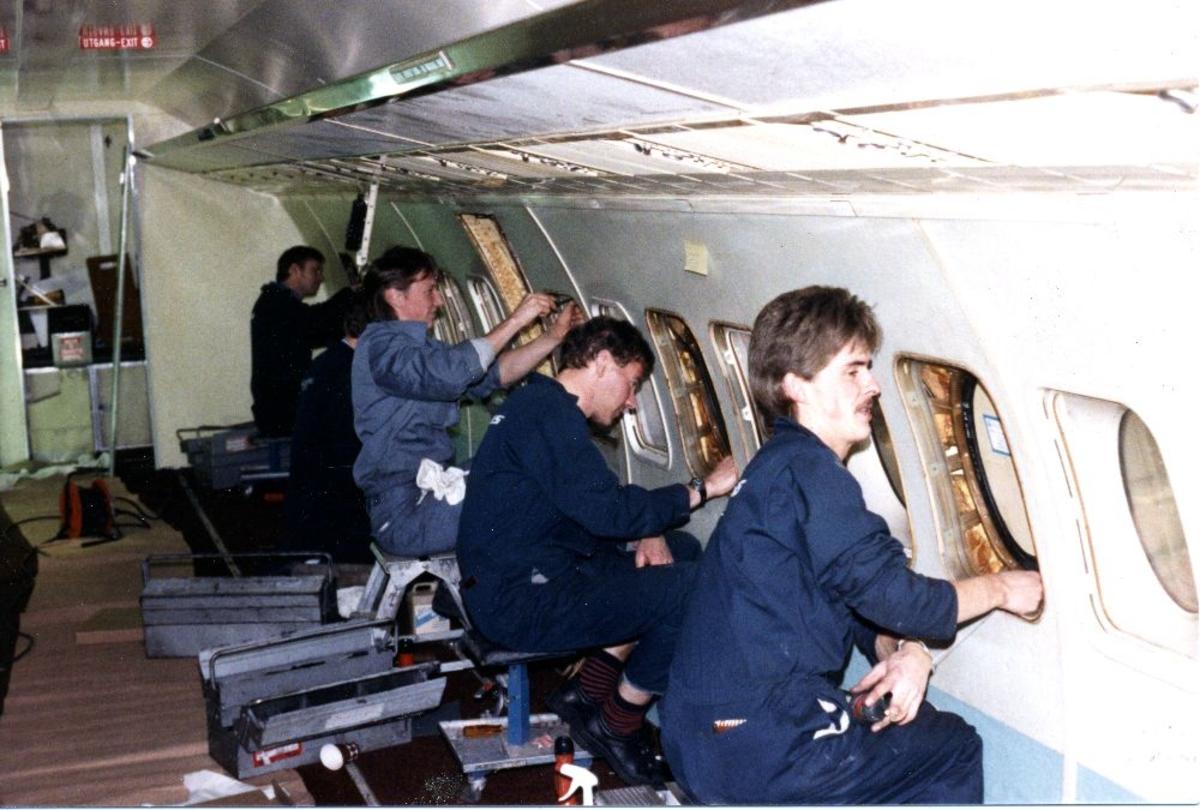 Lufthavn/flyplass. Sola/Stavanger. Braathens SAFE tekniske divisjon. Fra en flykabin. Flere personer i virksomhet med vedlikehold.