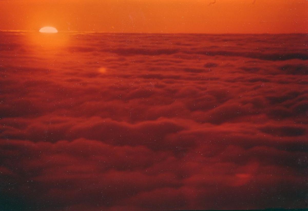 Luftfoto.Utsikt fra flyvinduet. Over skyene maler en dalende sol fantastiske farger.