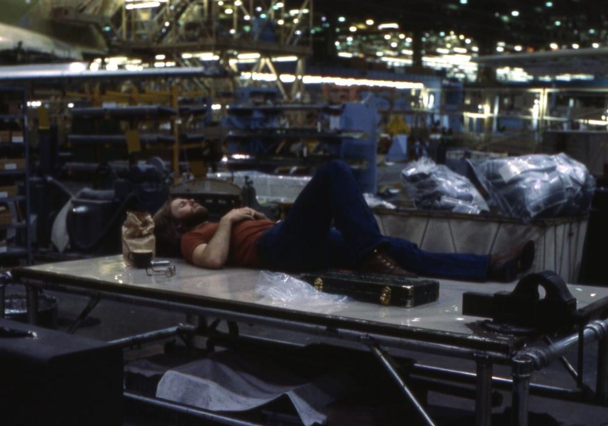 Landskap. Boeings flyfabrikk. Seattle. En person har inntatt horisontalen og slapper av mellom arbeidsøktene i produksjonslokalet.
