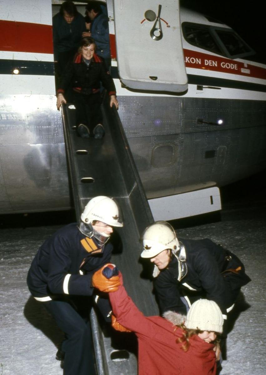 Lufthavn/Flyplass. Flere ansatte i Braathens SAFE trener på nødevakuering fra kabinen gjennom sklie til bakken.