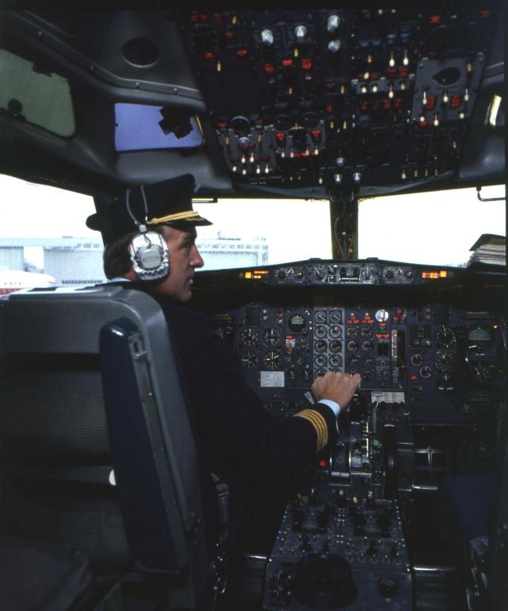 Lufthavn/Flyplass. I et fly fra Braathens SAFE ses Flykapteinen sittende i cockpit.