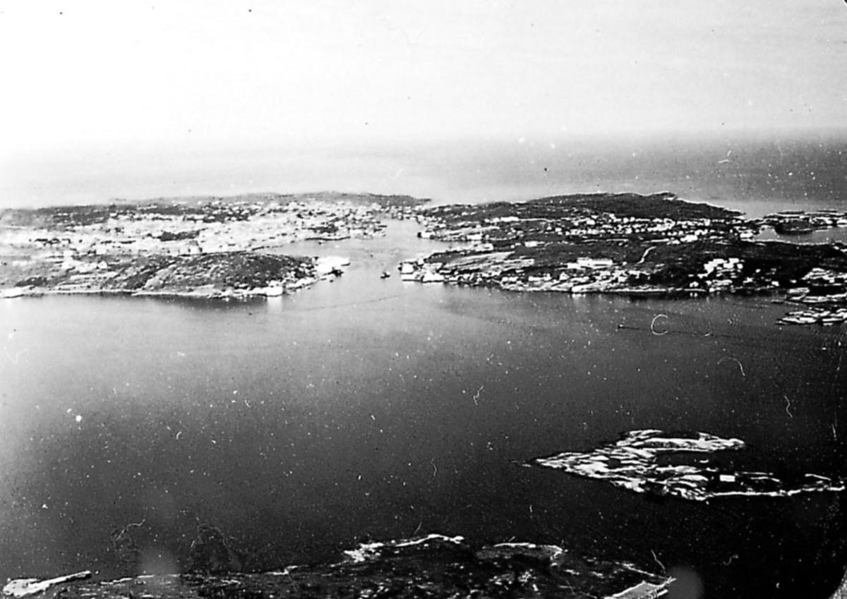 Luftfoto. Landskap med bebyggelse og hav under.