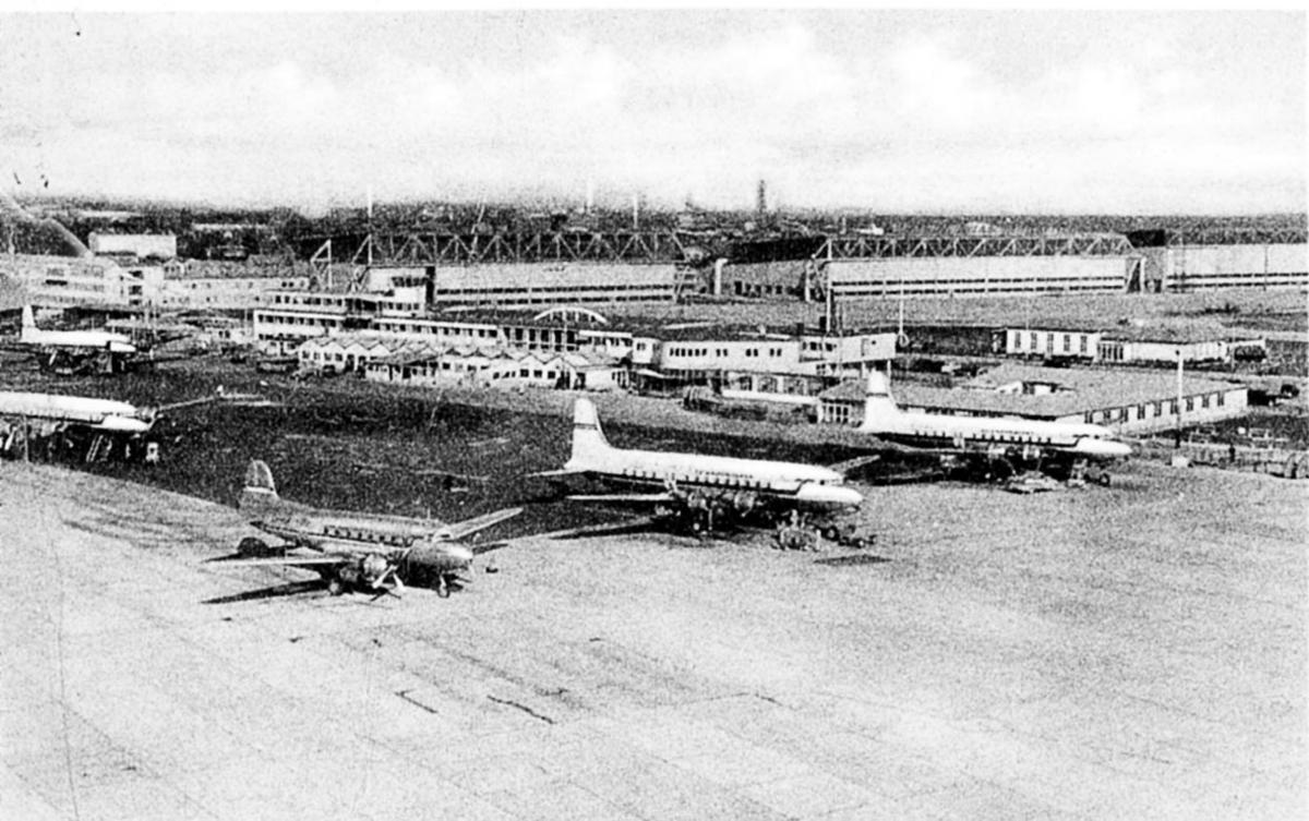 Lufthavn, fem fly på bakken. Flere personer ved flyene.