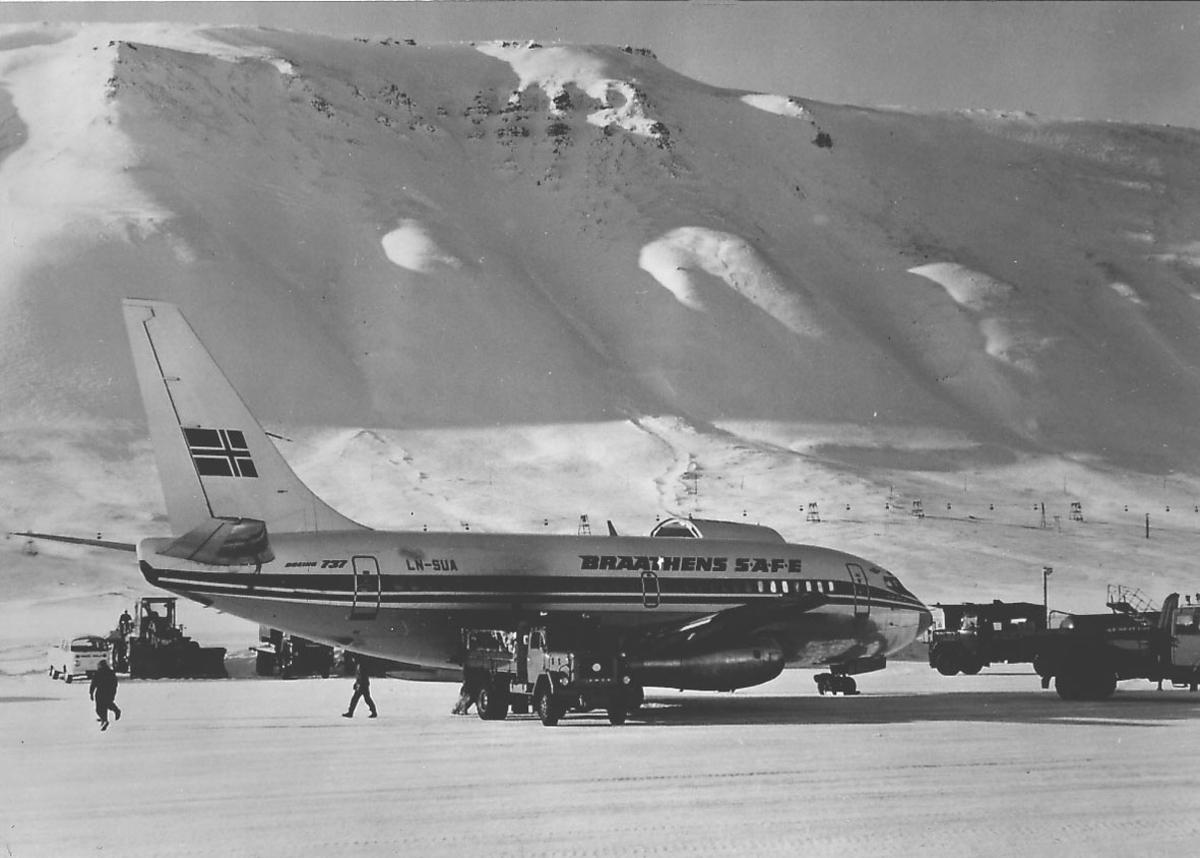 """Lufthavn. Ett fly på bakken, Boeing 737-200, LN-SUA """"Halvdan Svarte"""", fra BRAATHENS SAFE. Flere kjøretøyer og personer ved flyet. Snø på bakken."""