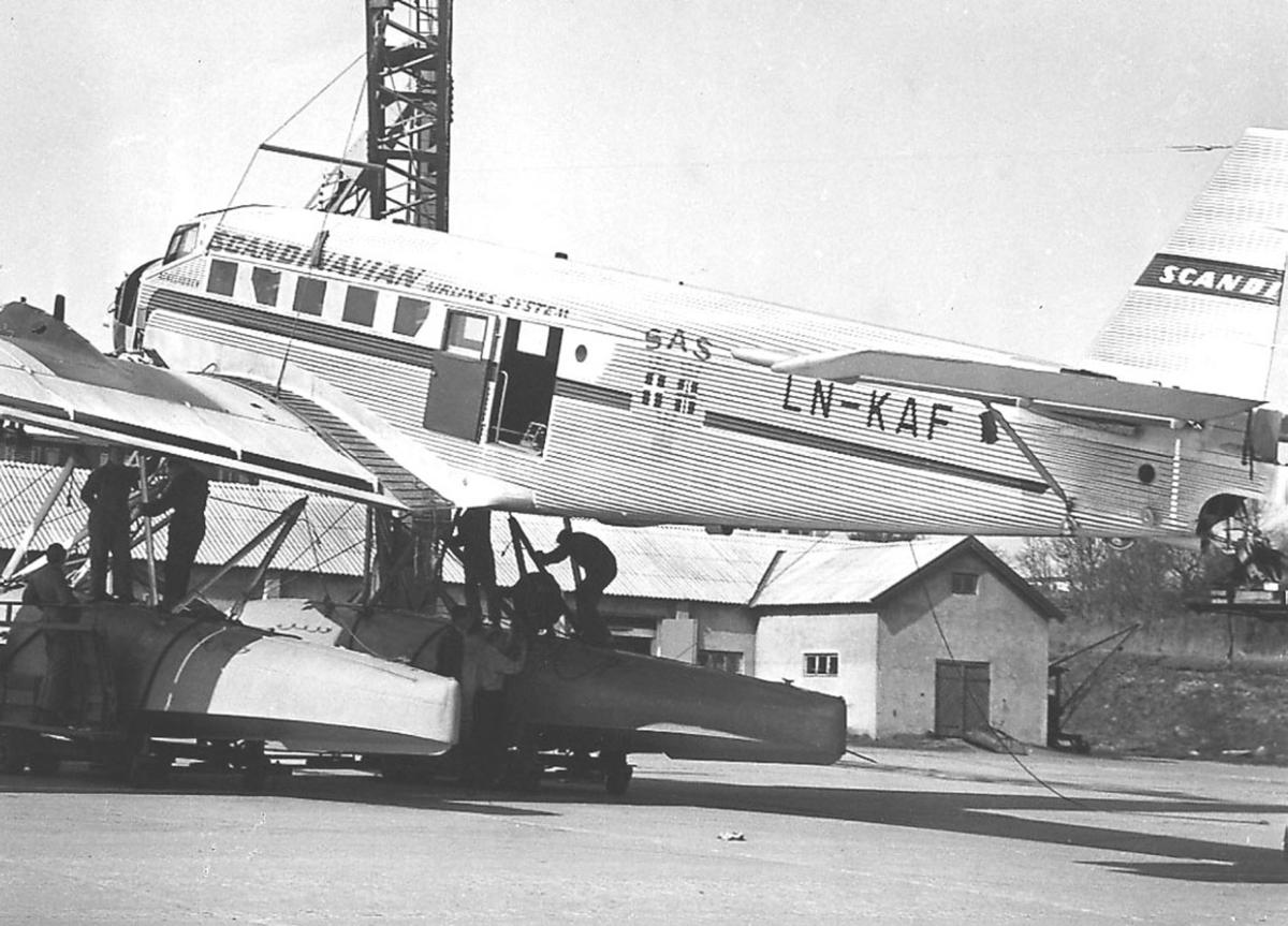 """Ett fly på bakken, Junkers Ju52/ 3mg2e, LN-KAF, """"Askeladden"""", fra SAS. Flere personer ved flyet."""