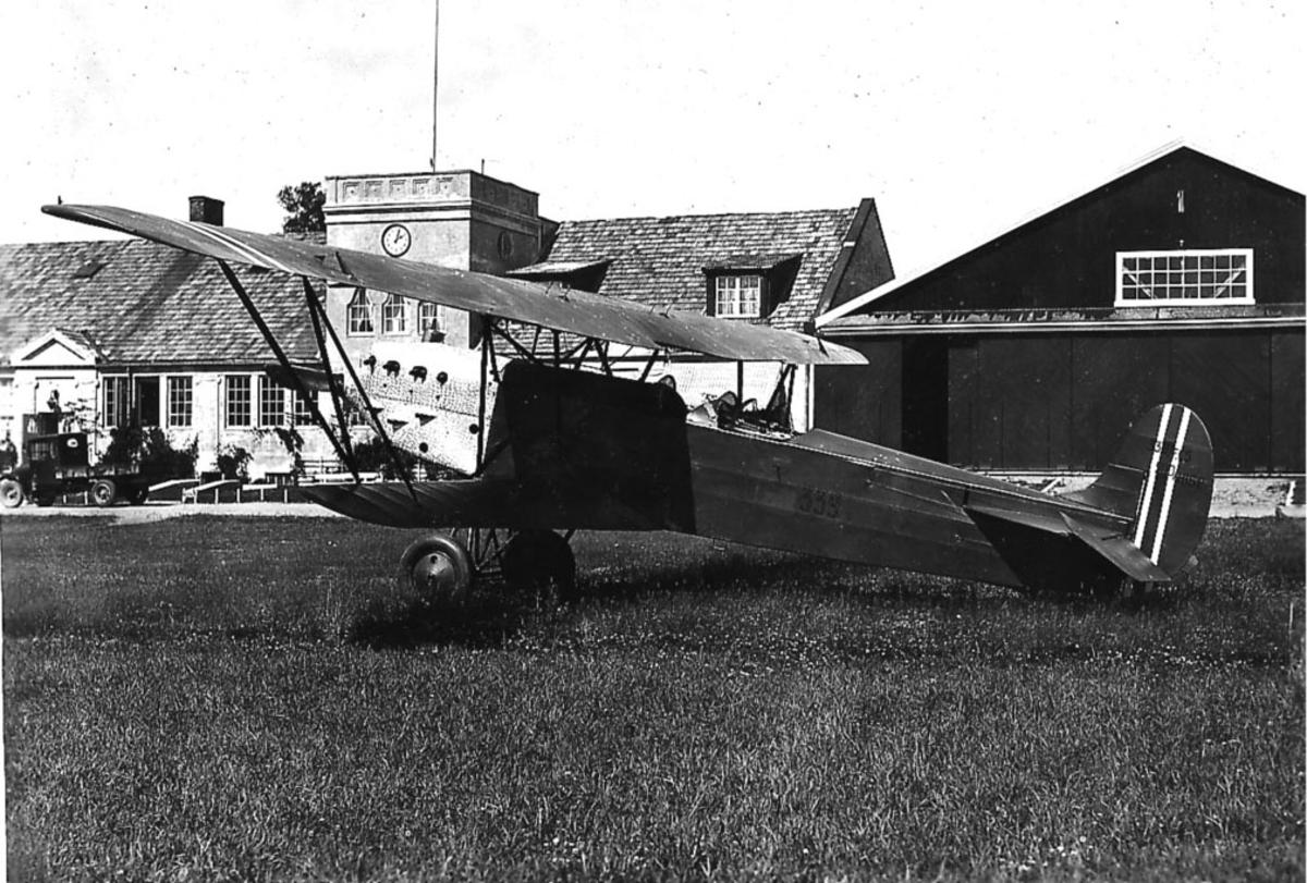 Kjeller lufthavn. En Fokker CVE nr 339 på bakken, bygninger i bakgrunnen