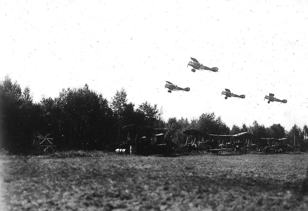 Luftfoto, fire fly i luften, Bristol Fighter nr 251, 257, 255 og 253 tar av. Kamuflerte fly, Avro 504, T1 og Kaje på bakken under.