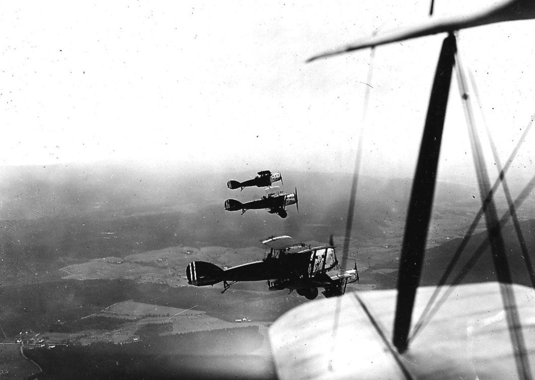 Luftfoto, fire fly i luften, Bristol Fighter. Noe av vinge og stag på ett fly, hvor bilde er tatt fra, i forgrunnen.