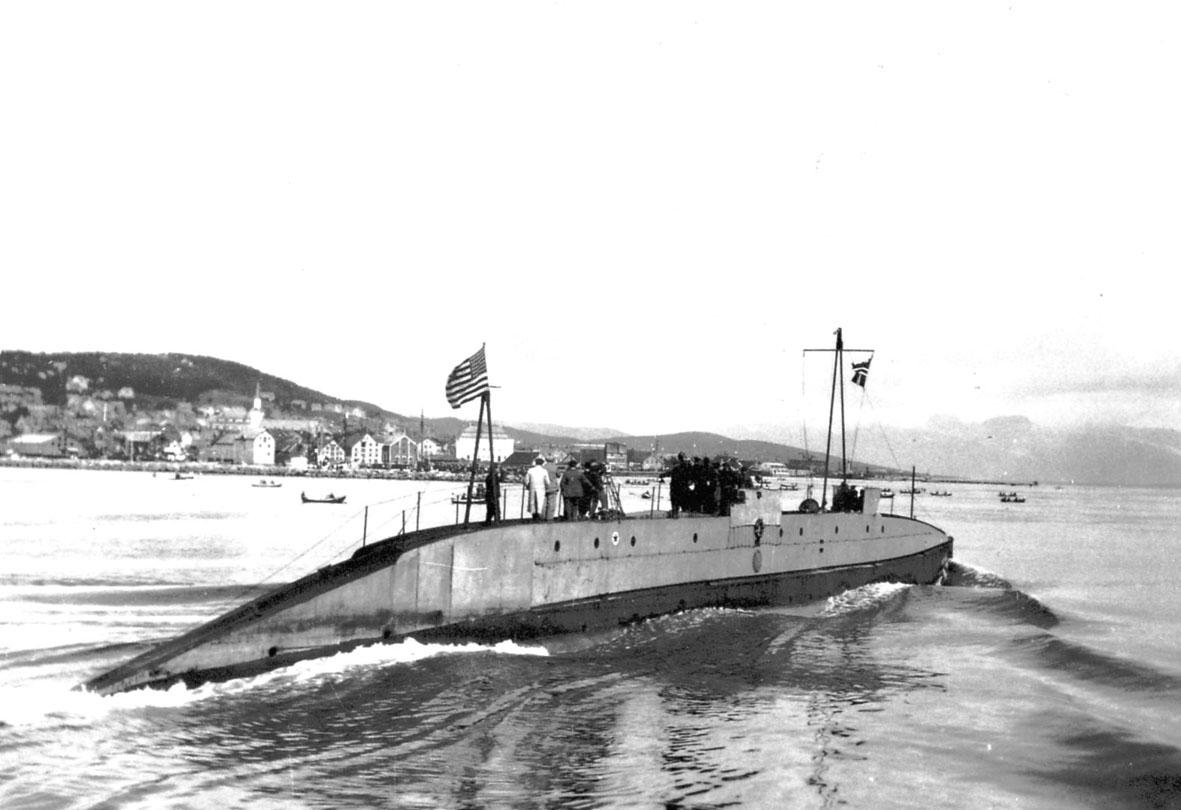 """Ubåten """"Nautilus"""" i sakte fart, bebyggelse bak, bl.a. ei kirke."""