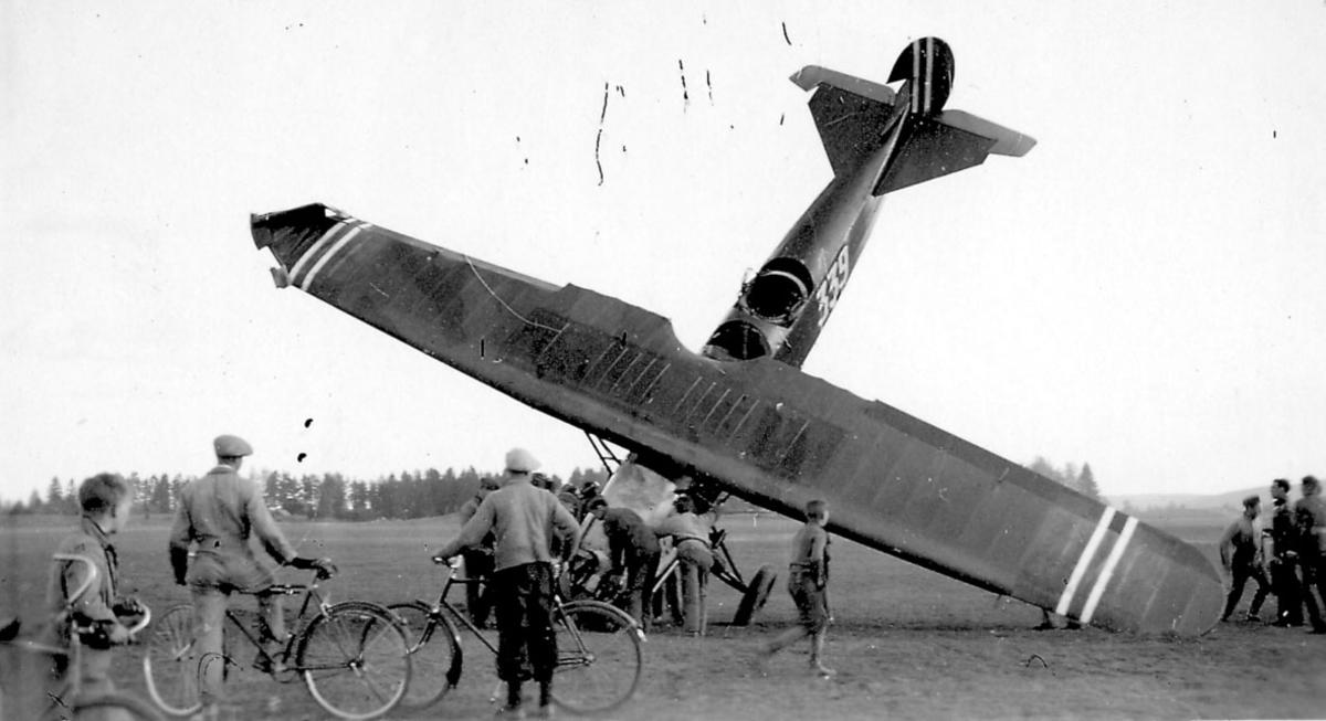 Åpen plass, ant. lufthavn. Ett fly, Fokker CVE, nr 339  står med nesepartien ned i bakken, havari. Flere personer ved flyet.