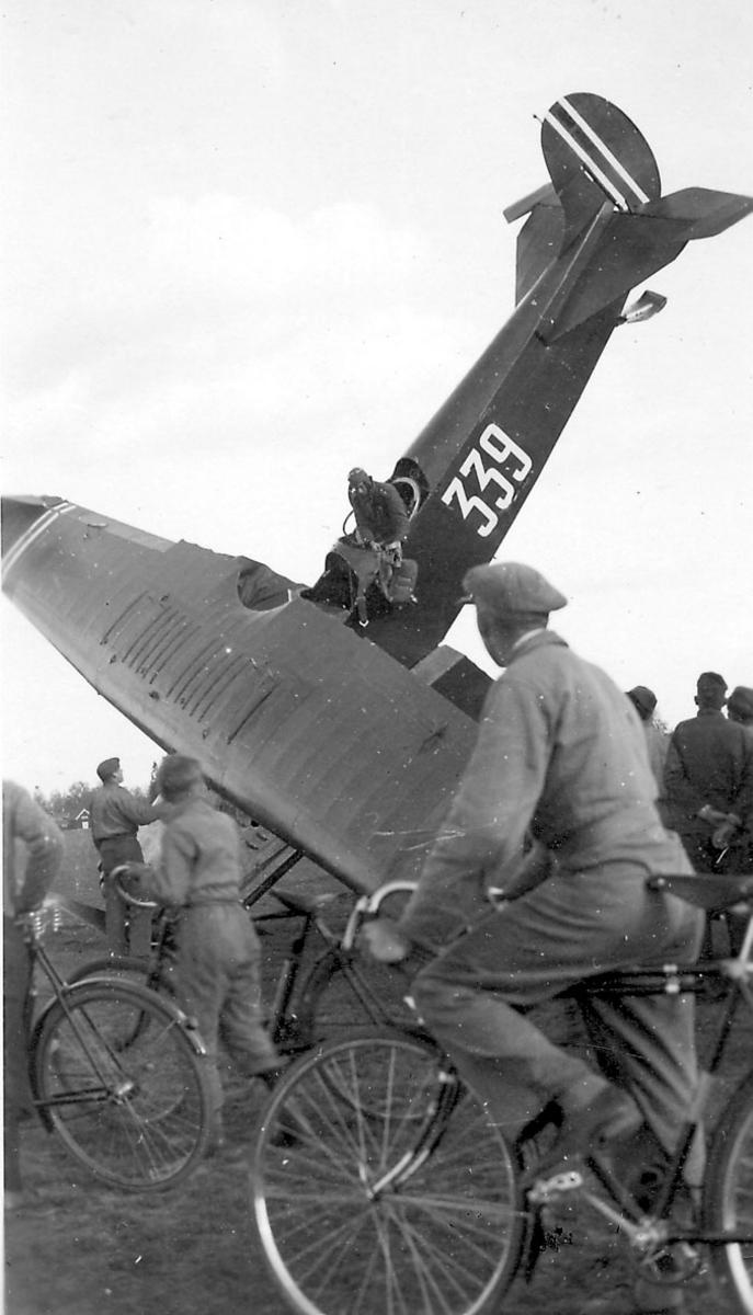 Åpen plass, ant. lufthavn. Ett fly, Fokker CVE ,nr 339 står med nesepartien ned i bakken, havari. Flere personer ved flyet.