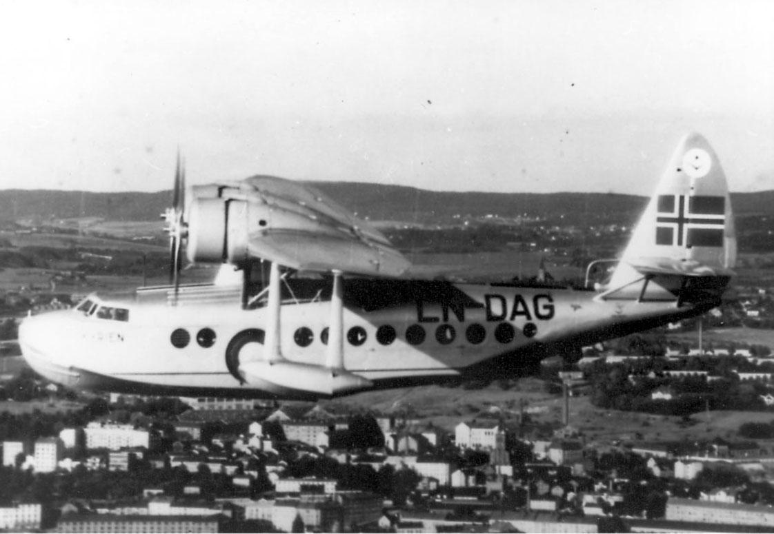 """Luftfoto. ett fly i luften, Sikorsky S.43, LN-DAG, """"Valkyrien"""".  Bebyggelse, tettsted  sees under."""