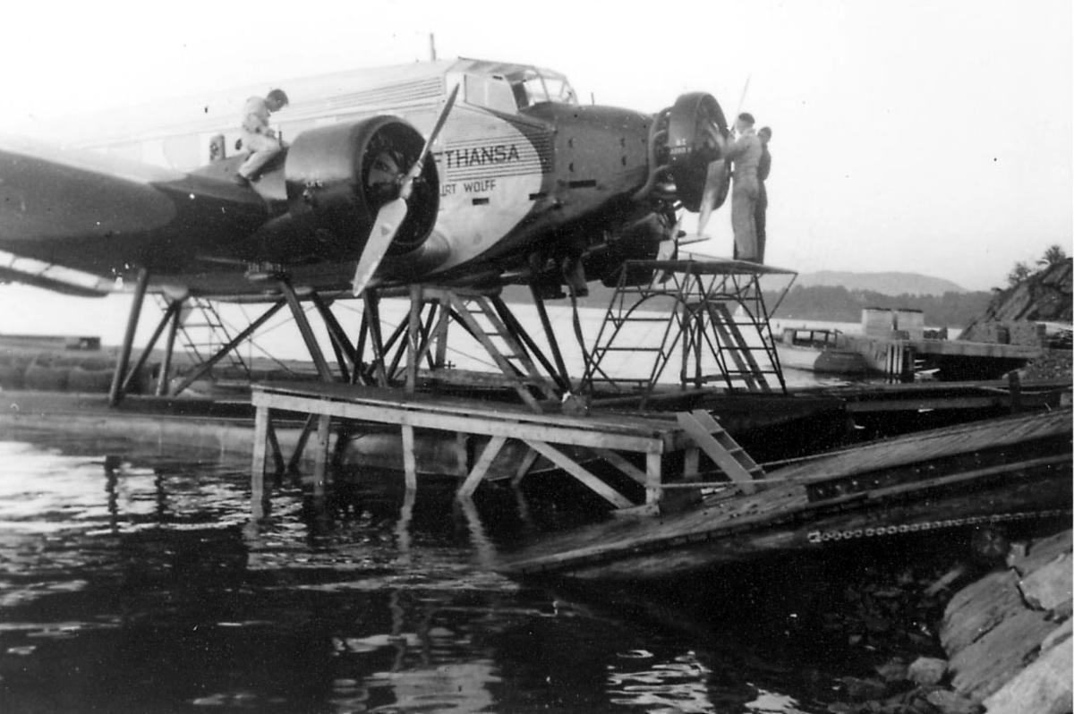 Sjøflyhavn, ett fly Junkers Ju 52/3mge fra Lufthansa. Ligger ved flytebrygge/kai. tre personer, mekanikere, arbeider på flyet.