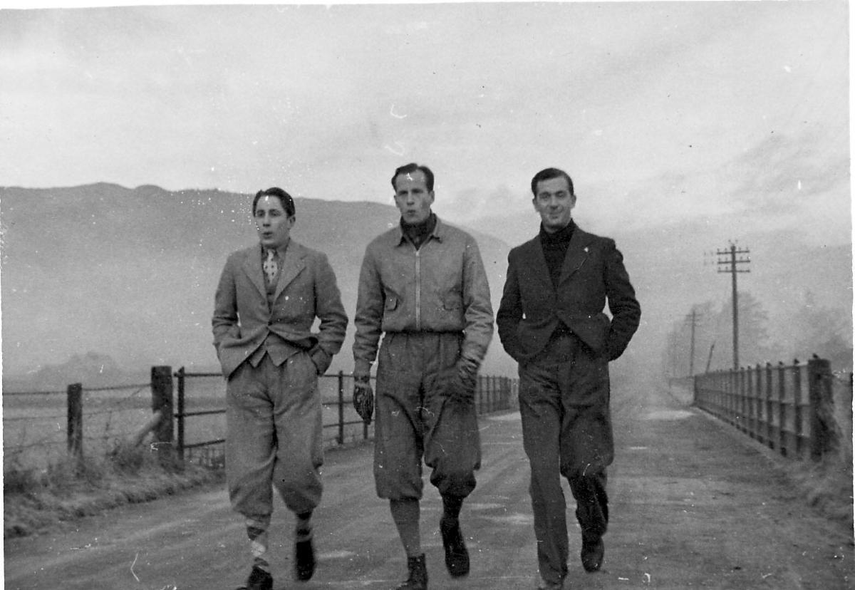 Portrett, tre personer går på en vei. Fjell i bakgrunnen.