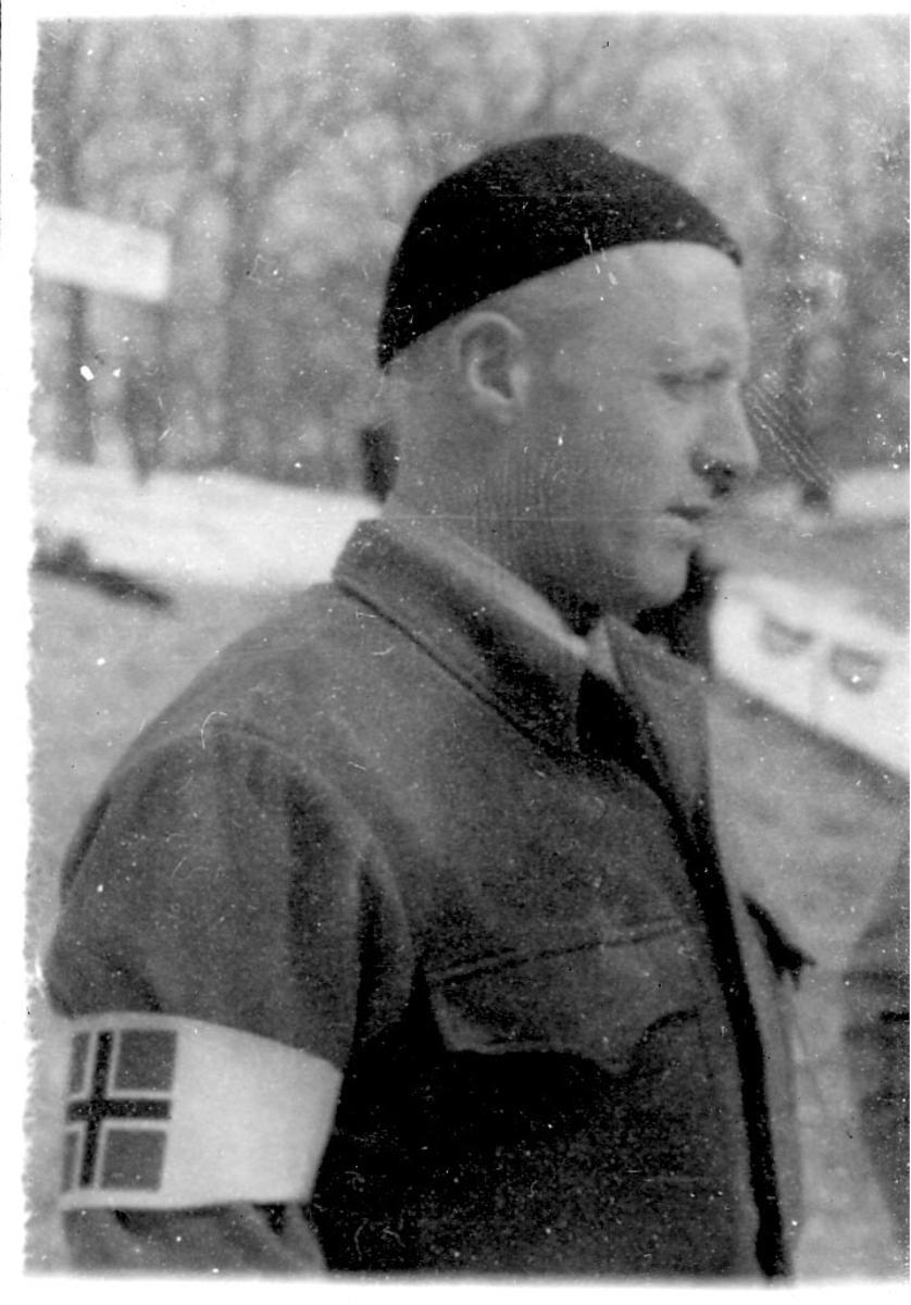 Portrett, en person i militæruniform. Hvitt bånd med det norske flagg på armen. Tatt utendørs.