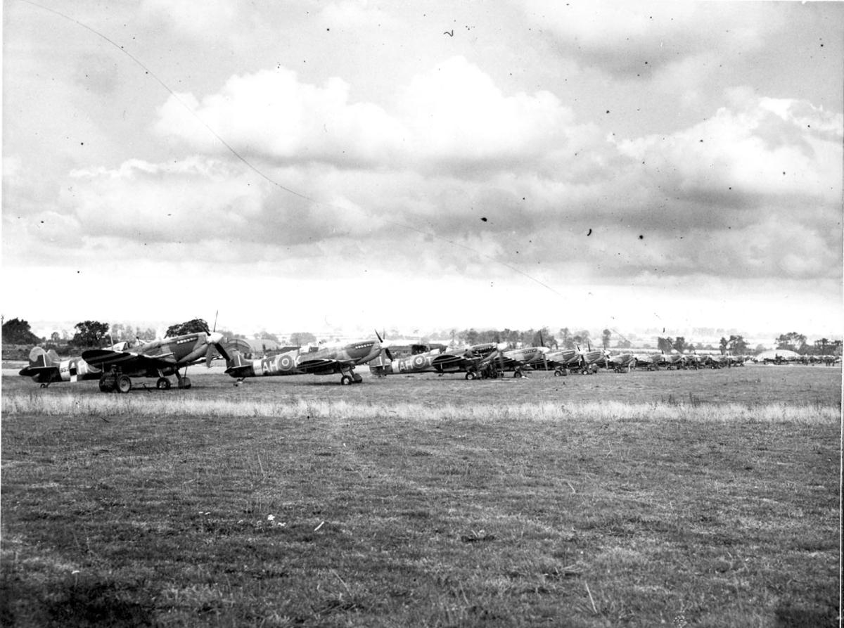 Åpen plass, ant. lufthavn, med mange fly oppstilt på rekke, Spitfire, skrått forfra.