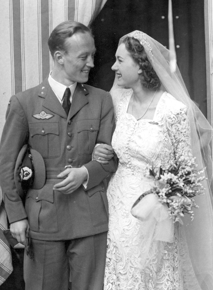Portrett, bryllupsbilde, tatt på trappa, ant. foran kirke. Mannspersonen i militæruniform, kvinnen i brudekjole.