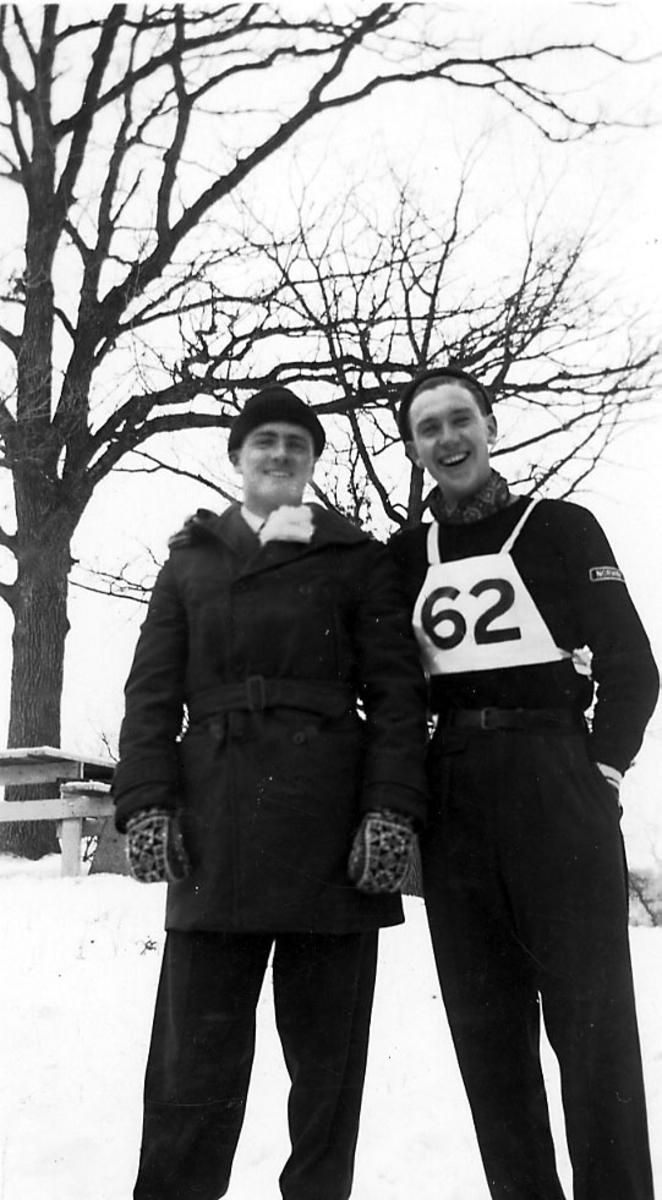 Portrett, to personer tatt utendørs, en av dem i skidress, ant. hoppdress med nr. 62 på brystet. Snø på bakken.