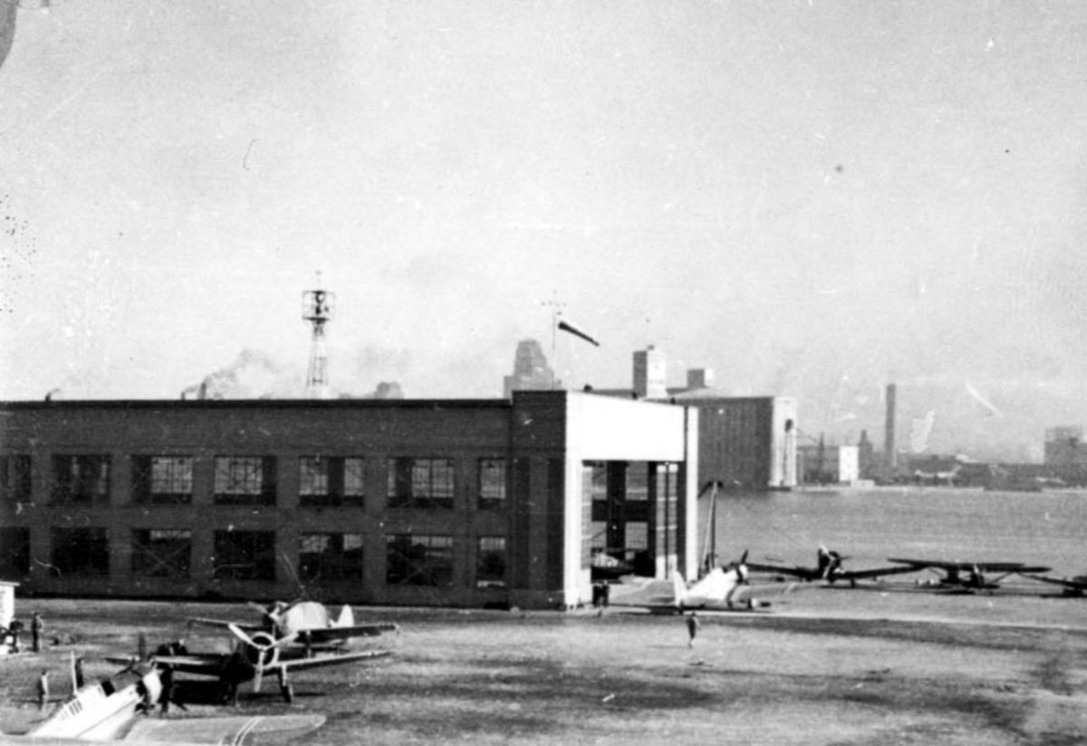 Åpen plass, ant. lufthavn. Bygning t.v. ant. hangar. flere fly på bakken. Havneområde bak og bebyggeslse, bygninger.