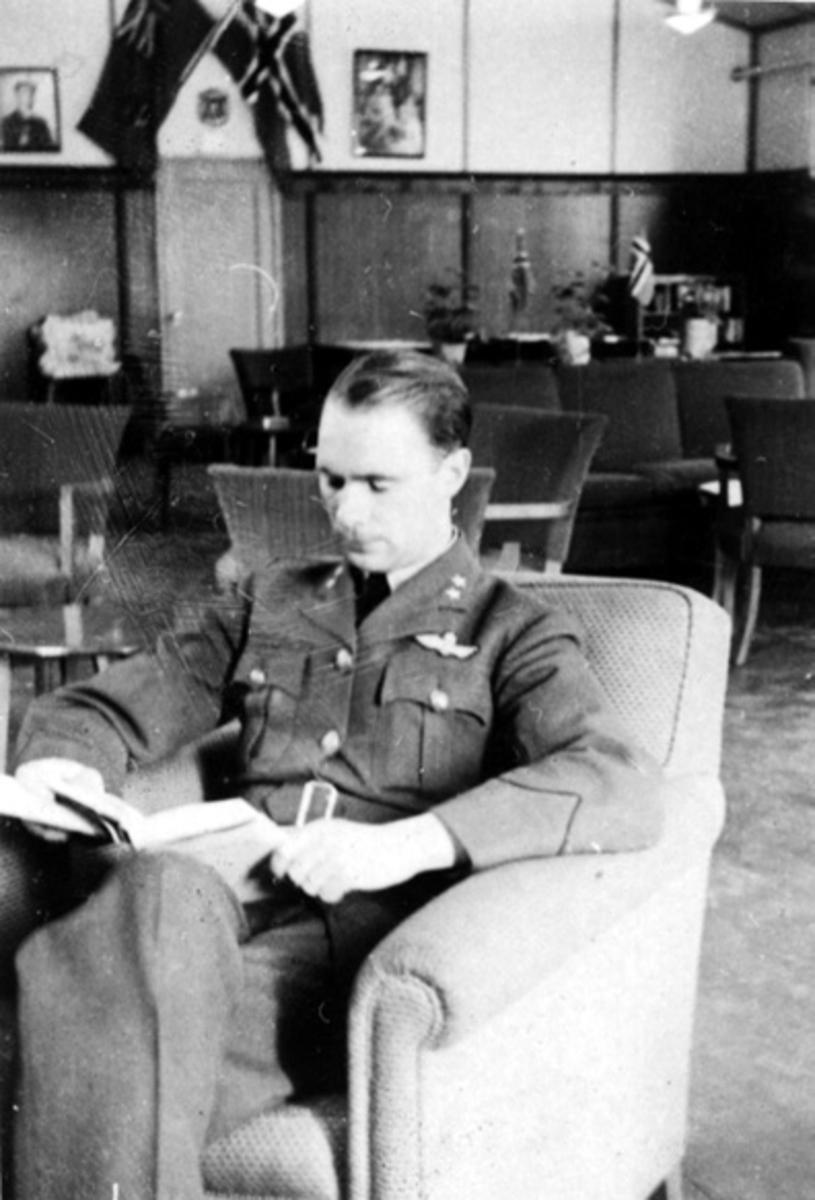 Portrett, en person, militære offiserer, i militæruniform sitter i en stol og leser. Tatt innendørs.