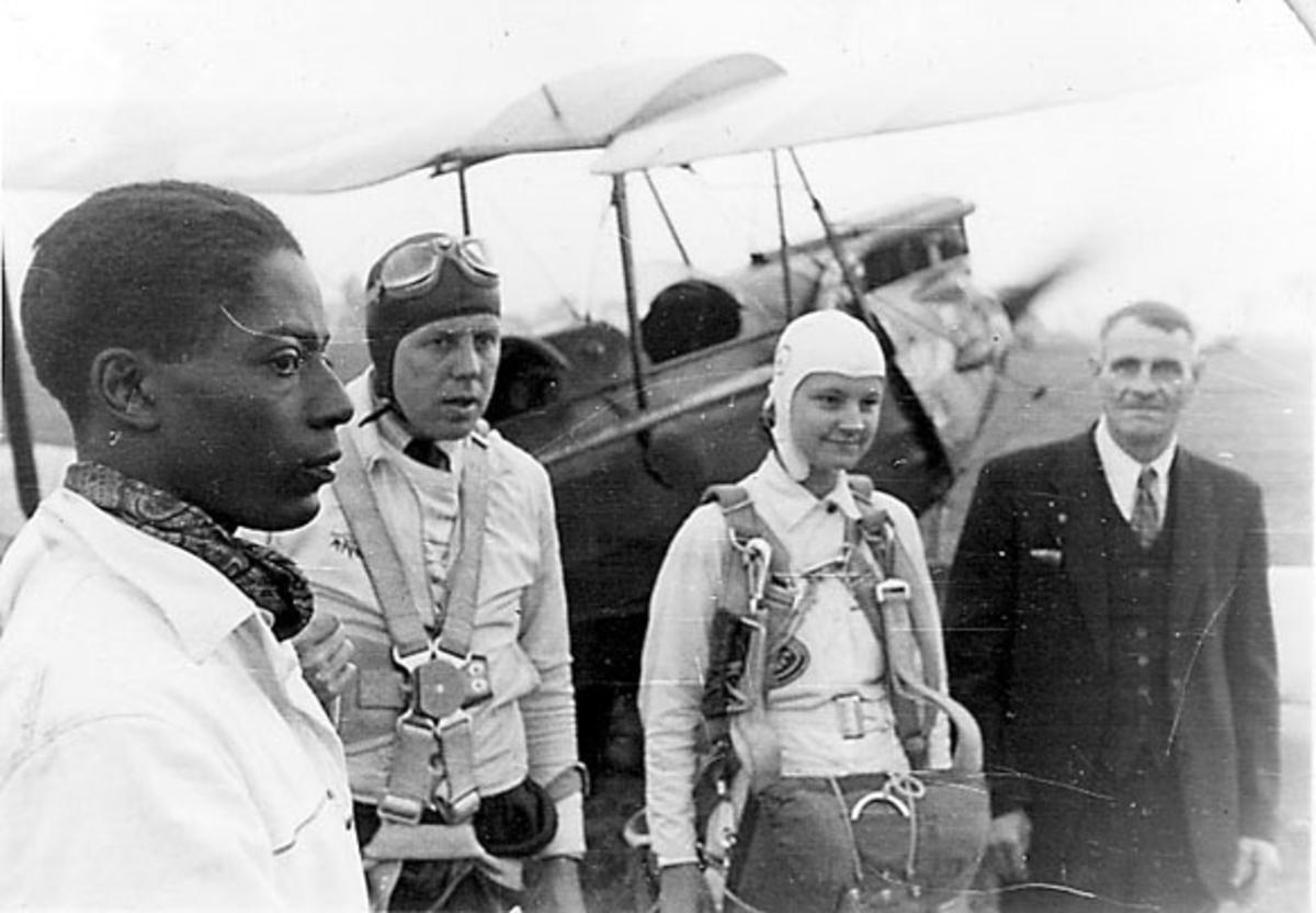 Portrett, flere personer foran et fly. 2 av personene i pilotuniform. (Den ene er ant. en kvinne).