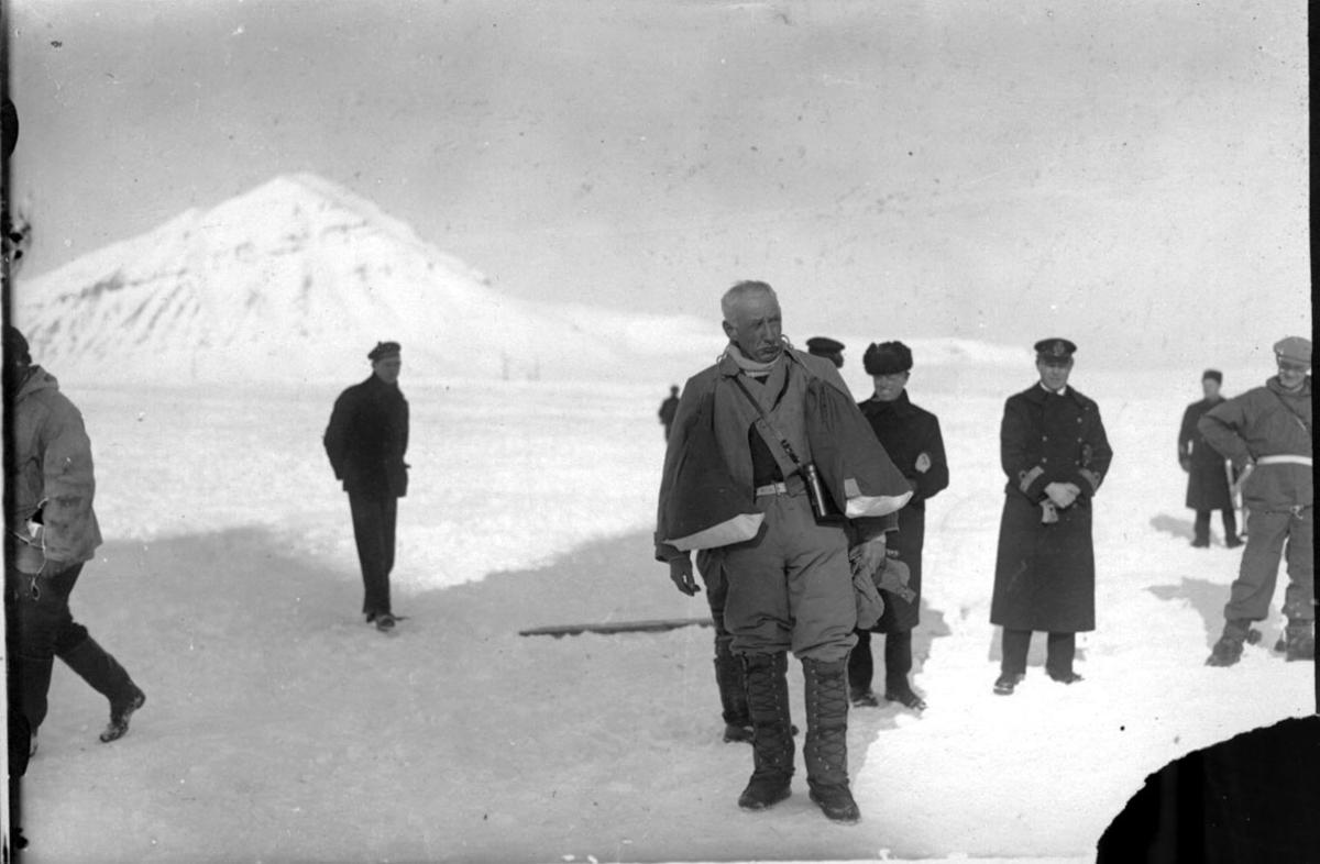 Flere personer utendørs, marineoffiser, matros osv. Snø på bakken, fjelltopp bak.