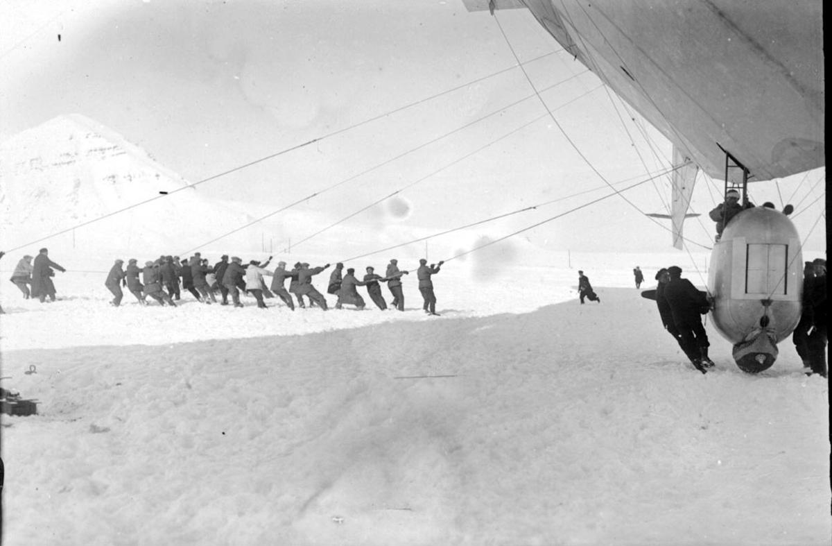 """Luftskipet """"Norge"""" i høyre billedkant. Flere personer i arbeid, drar i tau festet til luftskipet."""
