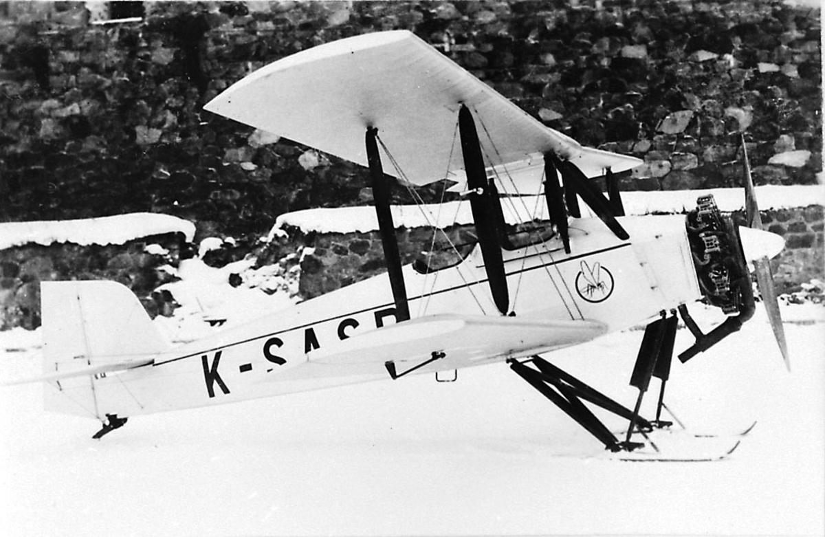 """Fly, propellfly, dobbeldekker, Sääski II. Flyet med skiunderstell, står på bakken. Snø. Logo av """"innsekt"""" foran på flyet."""