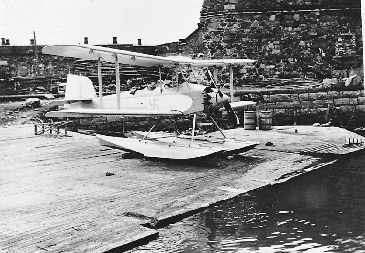 Fly, propellfly, dobbeldekker, Sääski II, med hakekors symbol på siden. Sjøfly som står på land nede ved havneområdet.