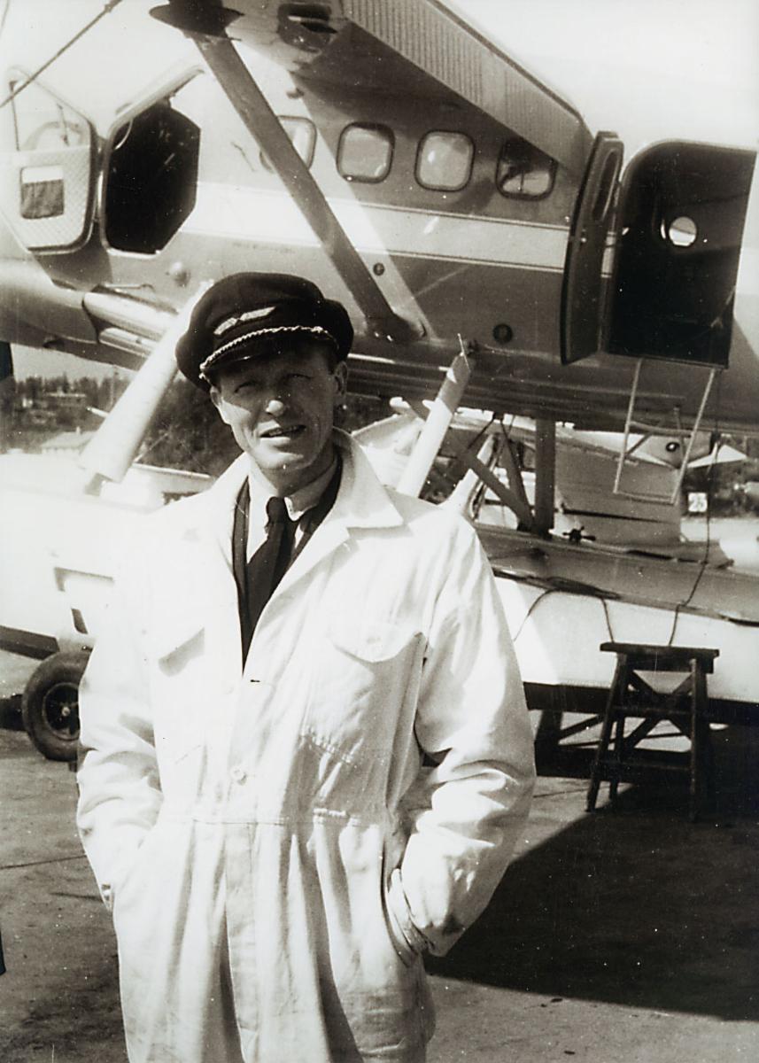 """Portrett, 1 person, står foran et fly, DHC-3 """"Singl Otter""""."""
