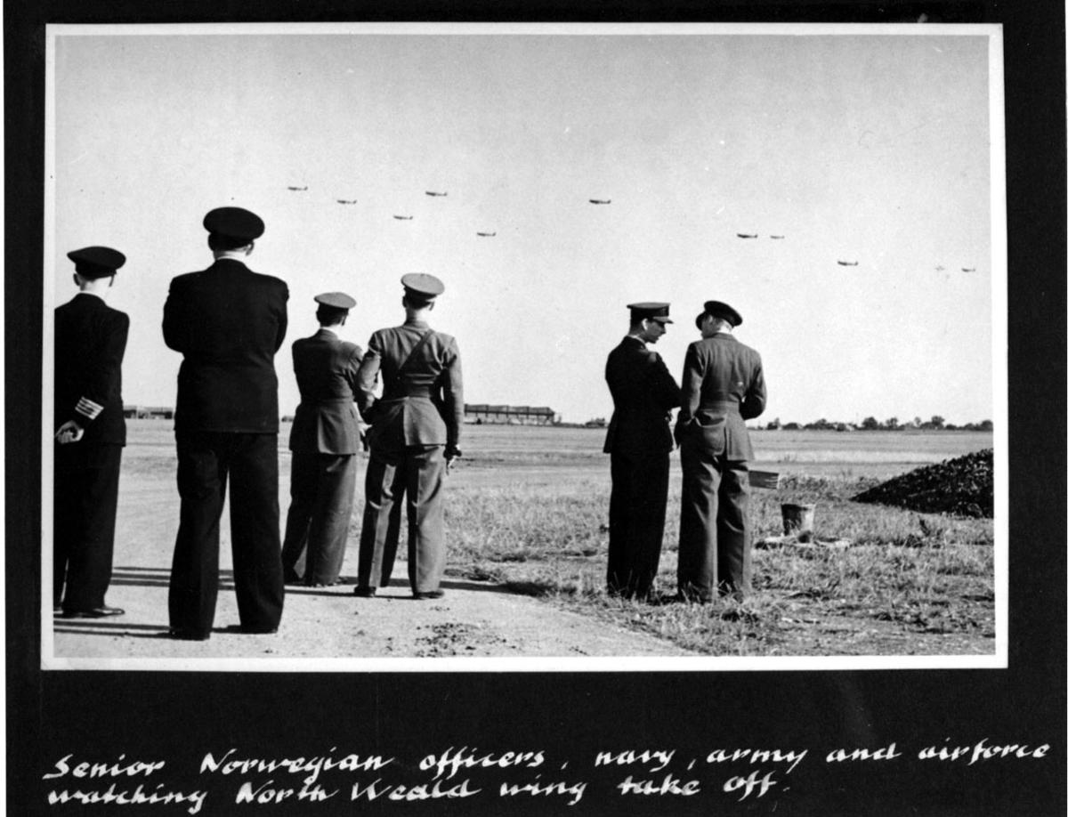 6 personer i militæruniform. Står og ser på fly som tar av. Håndskrevet engelsk tekst under bildet.