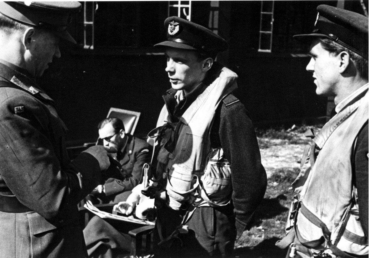 3 personer i militæruniform, 2 av dem med pilotutstyr. 2 personer sitter i stoler bak. Bygning i bakgrunnen.