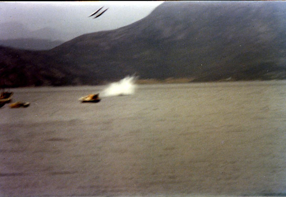 Vannsøyle, mindre båter i forgrunnen. Over henger to flotører i høyspentledning. Tilhører svensk sjøfly, propellfly, enmotors, Cessna 206,