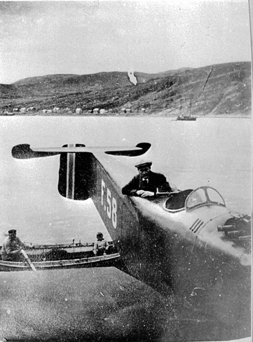 1 fly ved strandkanten, Hansa Brandenburg Monoplan Tractor W. 33. SFR. 2. Marinefly nr. 58. F. 58. Skrått forfra. En person ombord i flyet. Ved siden ligger en åpen robåt, med 2 personer ombord. Bak sees et fartøy og noen bygninger.