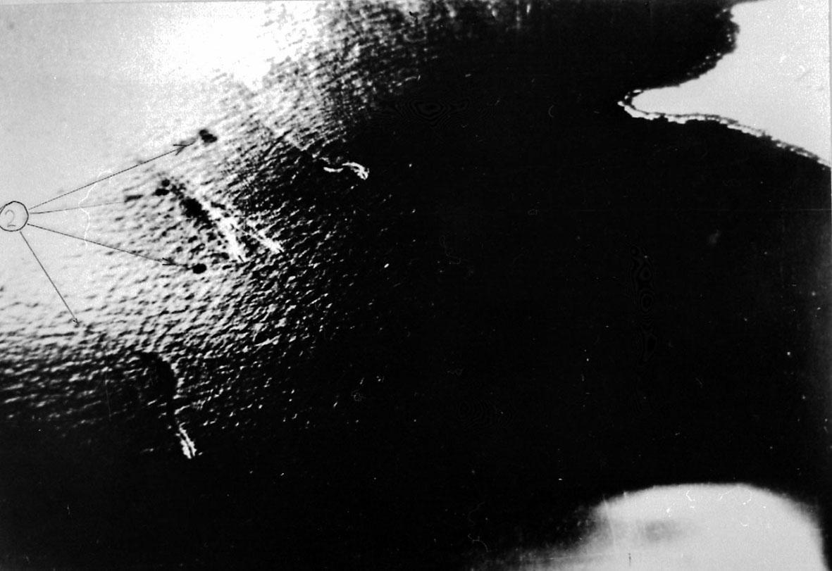 Flyfoto. Hav og litt av landskap t.h. Krusning på havoverflata etter ca 4 torpedoer, posisjonene tegnet merket med streker på bildet.