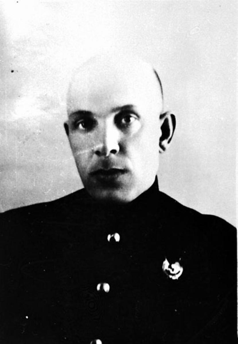 Portrett. En person i militæruniform, tatt innendørs. Noe russisk tekst på bildet.