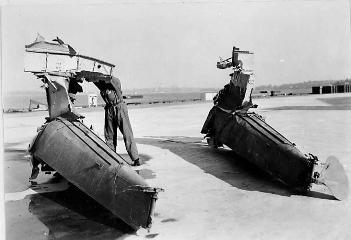 Flydeler, To personer holder i vrakrestene. Ant. havneområde bak. Rester av flottører ant. Northrop
