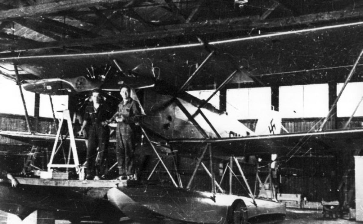 1 fly, MF-11, skrått forfra, inne i Marinens flyfabrikk. 3 personer oppstilt ved flymotoren. Hakekors på halepartiet. (Tyske kjennetegn).